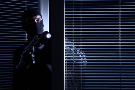 burglary and robbery. skillful professional masked burglar wears in balaclava, holding gun and torch and breaking into the house, isolated on black door window background.