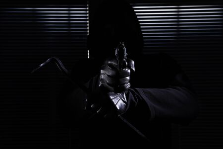 burglary and robbery. skillful professional masked burglar aiming the gun and crowbar and breaking into the house, hand close up on black window background. Stockfoto