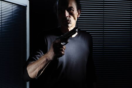 man with gun isolated on black door window, policeman, detective, bodyguard and self defense concept, otherwise robber, murderer and thief concept.