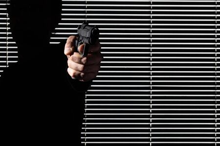 hand man aiming at gun isolated on black window, personal defense or theft and robbery concept.