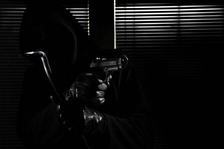 robo y hurto. ladrón enmascarado profesional hábil sosteniendo la pistola y la palanca e irrumpiendo en la casa, mano de cerca sobre fondo negro de la ventana.