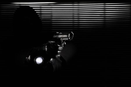 burglary and robbery. skillful professional masked burglar holding gun and torch and breaking into the house, hand close up on black window background.