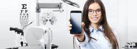concept of eye examination, smiling woman with spectacles showing mobile phone in office optometrist, contact us, appointment and customer support service concept, optician diagnostic equipments on background.