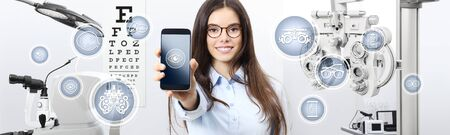 concept of eye examination, smiling woman with spectacles showing mobile phone icons in optometrist office, optician diagnostic equipments on background.