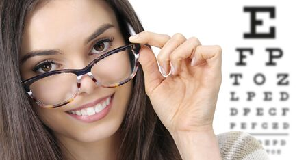 eye examination, woman smiling with spectacles isolated in optician office with eye chart on white background, prevention and control eyesight.