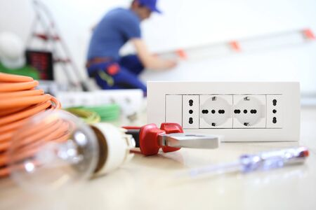 electrician work with electric equipment in the foreground, bulb, tools and socket, electric circuits, electrical wiring. Stok Fotoğraf