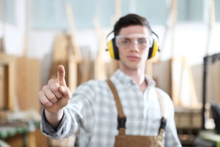 carpenter man touch screen on carpentry background.