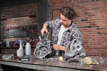 Mann, der mit dem Steckschlüssel arbeitet, Motorteile auf der Werkbank in der Heimgaragenwerkstatt repariert und reinigt, DIY-Konzept. Standard-Bild