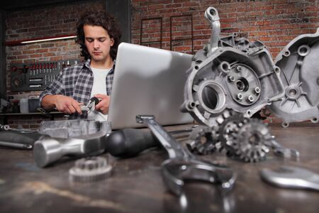 man working with caliper to measure the motor gear, study on the computer and search the internet