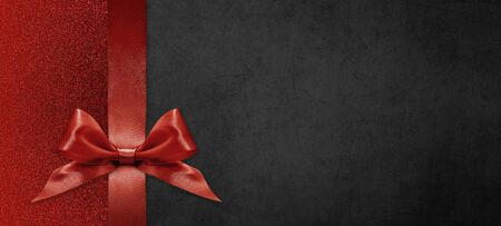 gift card wishes merry christmas background with red ribbon bow on black shiny vibrant color texture template with blank copy space. Stock Photo