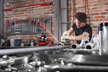 man work in home workshop garage with angle grinder, goggles and construction gloves, metal grinder makes sparks, diy and craft concept.