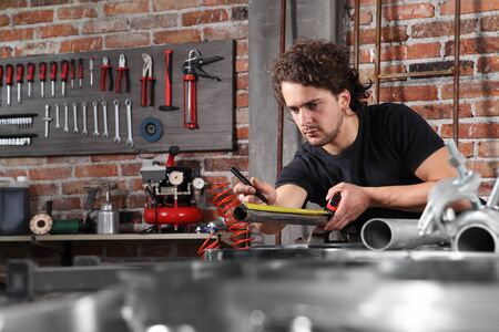man work in home workshop garage measure metal with tape meter, iron pipe marker on the workbench full of wrenches, diy and craft concept. Stock Photo