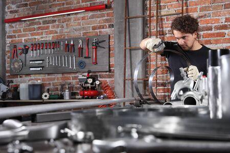 Mann in Heimwerkstatt Garagenarbeit Metall mit Griff Drahtbürste, Reparatur, Bürsten und Reinigungseisen Federspirale auf der Werkbank