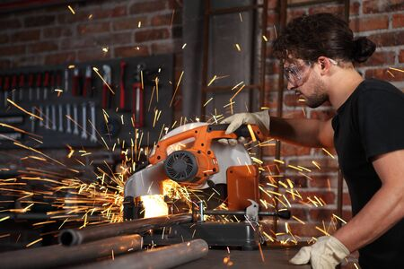man work in home workshop garage with miter saw, goggles and construction gloves, sawing metal pipe makes sparks, diy and craft concept. Stok Fotoğraf