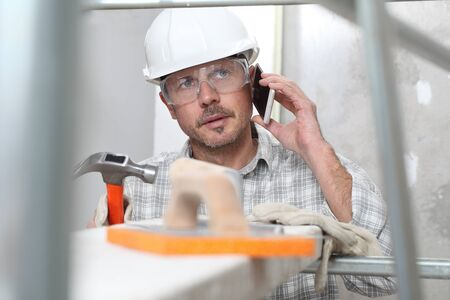 man work, professional construction worker with mobile cell phone, plastering tools on scaffolding, safety hard hat, gloves and protective glasses. on interior building site background. Standard-Bild
