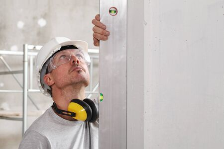 man worker looks at the spirit level checks the wall with hard hat, glasses and ear protection headphones, white wall with copy space. Stock Photo