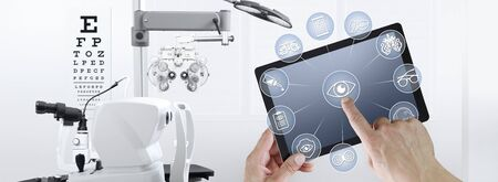 hands touch screen of digital tablet with ophthalmologist and optometrist icons symbols, ophthalmology and optometry equipment on background. Zdjęcie Seryjne