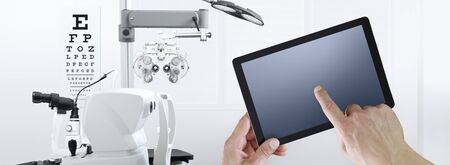 eye examination test concept, hands touch screen of digital tablet, ophthalmology and optometry equipment on background.