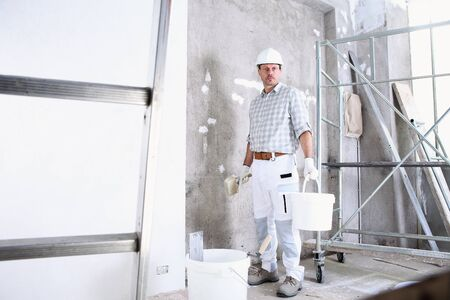 plasterer man work holds a bucket and use the brush wet the wall before application to interior construction site wear helmet and protective gloves, ladder and scaffolding on background.