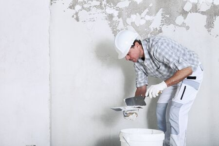 plasterer man at work, take the mortar from the bucket to plastering the wall of interior construction site wear helmet and protective gloves, isolated with copy space on wall.