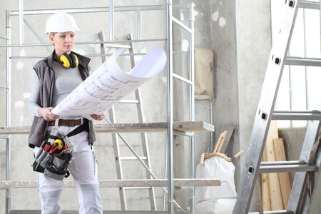 woman construction worker builder looking at bluprint, wearing helmet, hearing protection headphones and tools belt bag in building site indoors background.
