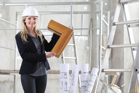 smiling woman architect or construction interior designer with wooden windows cutaway inside a building site with ladder and scaffolding in the background. Banque d'images