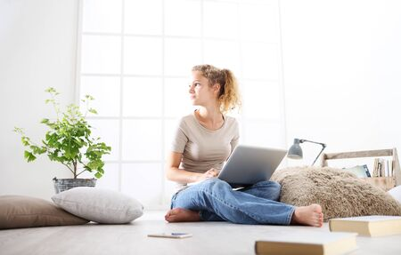 young woman sitting in living room at the computer, stay at home concept.