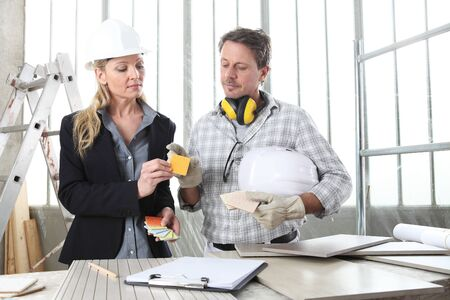 man and woman architect interior designer and foreman worker together with color samples and decorative materials discussing the project for interior decoration in the inside the construction building site