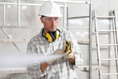 man worker measure with meter tape wear hard hat, glasses and hearing protection headphones, at construction site