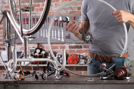 man repair the vintage bicycle in garage workshop on the workbench with tools, diy concept Archivio Fotografico