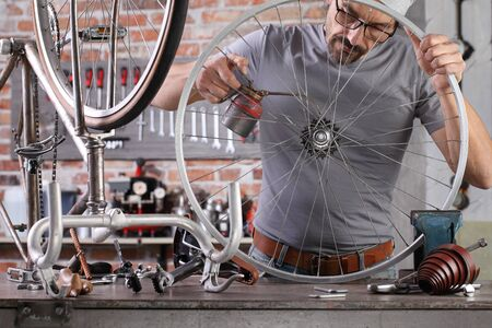 man repair the vintage bicycle oil gears in garage workshop on the workbench with tools, diy concept Stockfoto