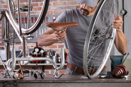 man repair the vintage bicycle in garage workshop on the workbench with tools, diy concept.