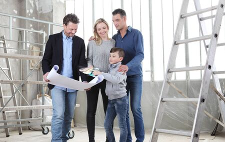 Architect showing house design plans to a family with child. Meeting at interior construction site to talk about house appearance, interior decoration, home layout and wall colors.