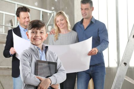 Architect showing house design plans to a family with smiling happy child with digital tablet. House building goal concept. Meeting at interior construction site to talk about house appearance, interior decoration and home layout.