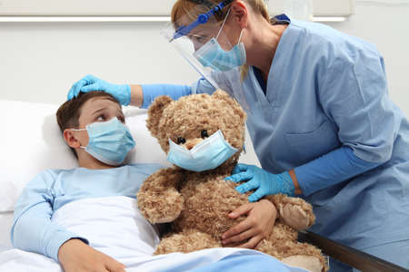 nurse with thermometer measures fever on patient child in hospital bed, wearing protective visor and surgical mask, corona virus covid 19 protection concept, Reklamní fotografie