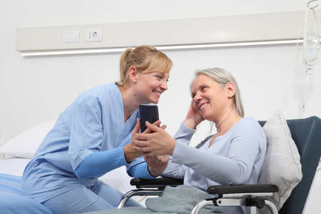 nurse helps with cell phone to contact the elderly lady's family in the wheelchair near bed in hospital room, concept of loneliness and old age diseases