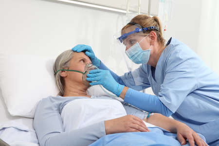 nurse puts oxygen mask on elderly woman patient lying in the hospital room bed, wearing protective gloves and visor medical mask, coronavirus covid 19 protection concept