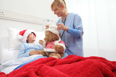 Christmas holiday in hospital happy child lying in bed with Santa Claus hat and nurse dressing a teddy bear Stock Photo