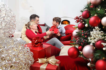 merry christmas, happy family at home, parents giving the gift to their child near the illuminated and decorated tree, joyful and smiling sitting in the living room and comforted by the fireplace Standard-Bild