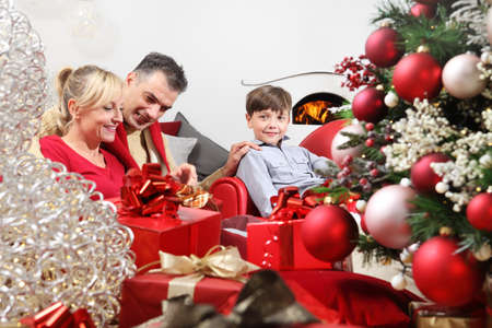 merry christmas, happy family at home, parents giving the gift to their child near the illuminated and decorated tree, joyful and smiling sitting in the living room and comforted by the fireplace Stockfoto