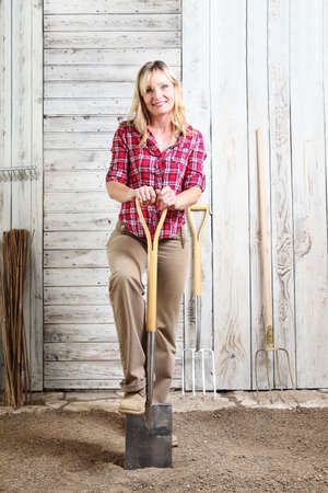 woman in vegetable garden with the spade isolated on white wooden shed background with gardening tools