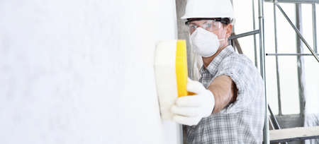 man builder using a sponge on wall professional construction worker with mask, safety hard hat, gloves and protective glasses. interior building site, copy space background