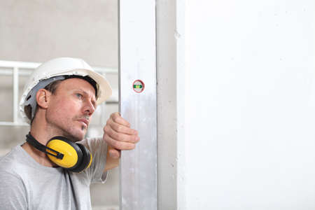 man worker looks at the spirit level checks the wall with hard hat and ear protection headphones, white wall with copy space Stock Photo