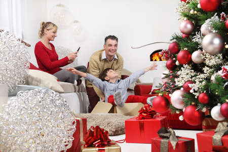 merry christmas, happy family at home, mom with cell phone photographs dad and son playing near the illuminated and decorated tree, joyful and smiling sitting in the living room comforted by fireplace Stockfoto