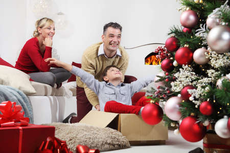 merry christmas, happy family at home, mom and dad play with their son near the illuminated and decorated tree, joyful and smiling sitting in the living room and comforted by the fireplace