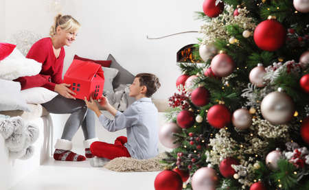 merry christmas, happy family at home, mom and son with gift near the illuminated and decorated tree, joyful and smiling sitting in the living room and comforted by the fireplace
