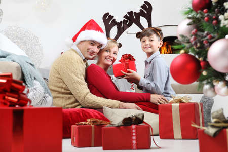 merry christmas, happy family stay at home, parents giving the gift to their child near the illuminated and decorated tree, joyful and smiling sitting in living room and comforted by the fireplace