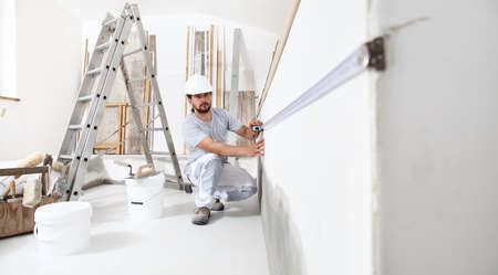 construction worker plasterer man measuring wall with measure tape in building site of home renovation with tools and building materials on the floor