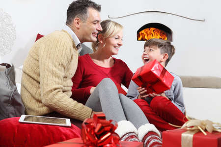 merry christmas, happy family stay at home, parents giving the gift to their child, joyful and smiling sitting in the living room and comforted by the fireplace