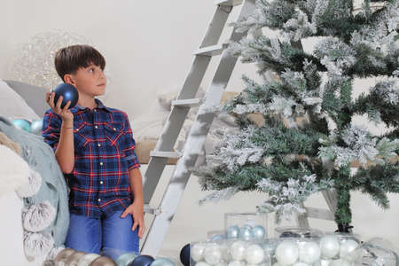 child decorate the christmas tree with balls and ladder at home